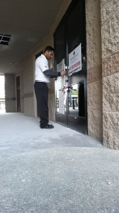 Security Guard Checking Commercial Building Door To Make Sure It Is Secure